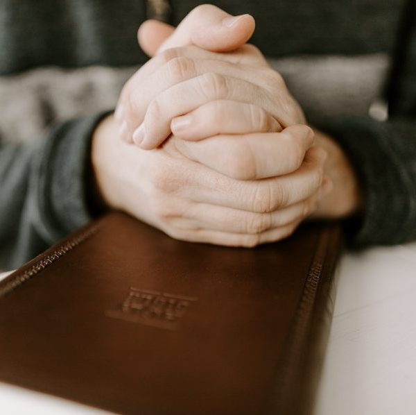 praying hands over holy bible